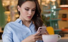 Wanita cantik bermain smartphone di cafe